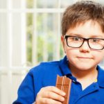 Portrait of a blond kid enjoying a chocolate bar at home