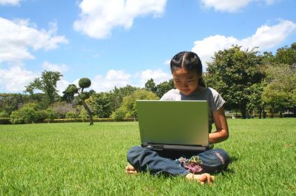 summer-child-on-computer-on-grass